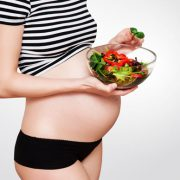 Healthy nutrition and pregnancy. Close-up pregnant woman's belly and vegetable salad